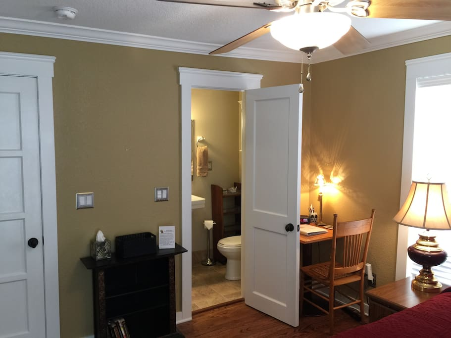 The en suite room, which has a convenient work desk,  is a corner room with plenty of light. The bath is through the door.