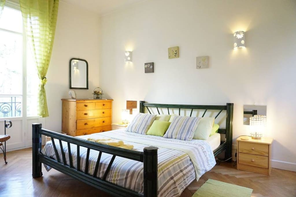 Spacious King size bedroom with french doors and balcon on one side and a window to the internal courtyard on the other