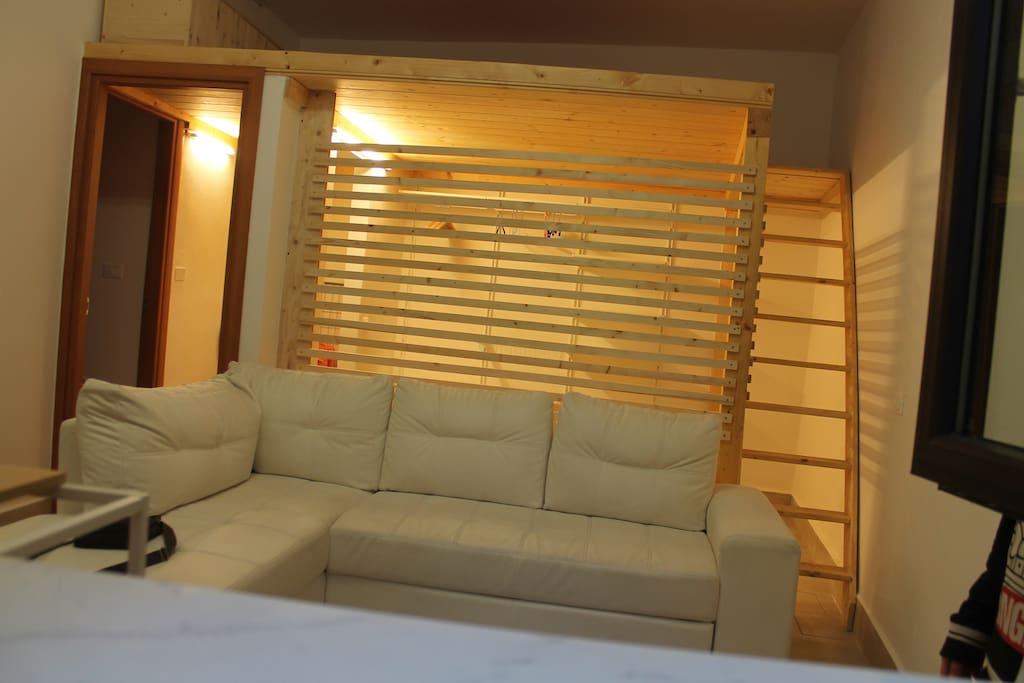 il divano letto e la cabina armadi, con la scala in legno per accedere al soppalco