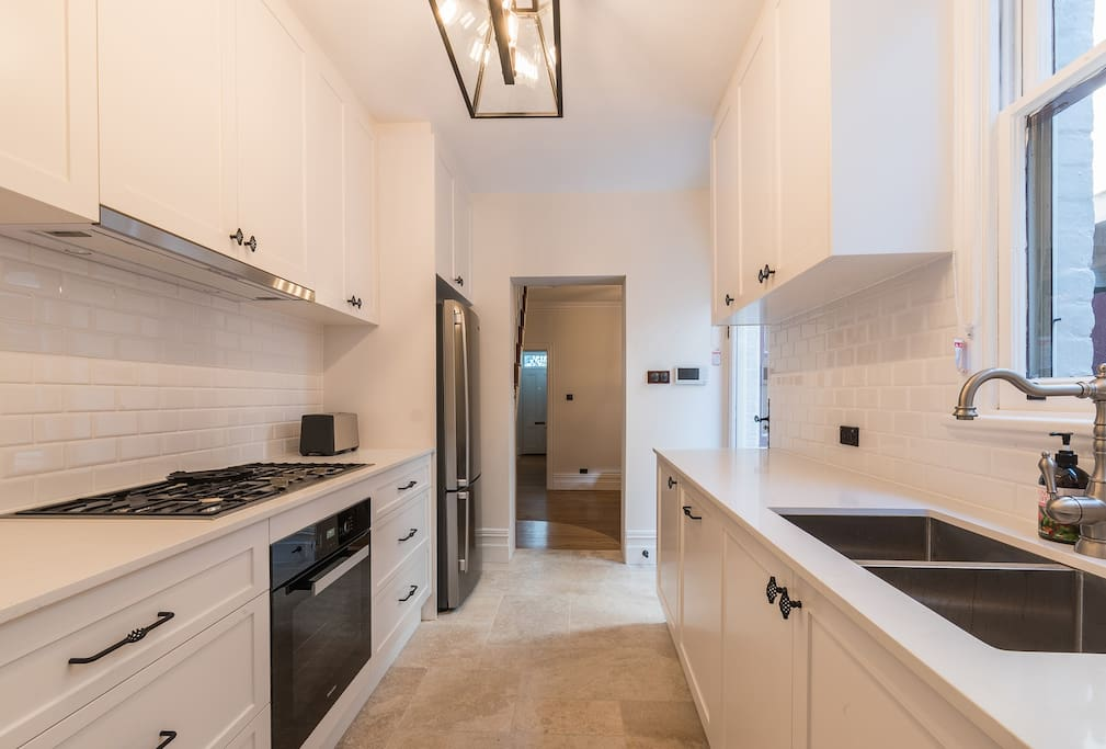 Beautiful kitchen with new appliances and stone floors
