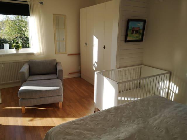 Sovrum 1 nedervåning med spjälsäng som har täcke och kudde.