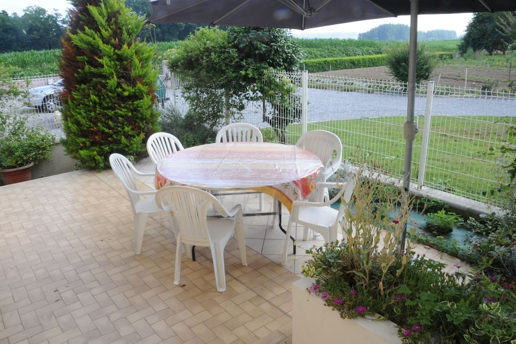 Terrasse privative, avec table ronde de 8 à 10 personnes, fauteuils, parasol et barbecue.