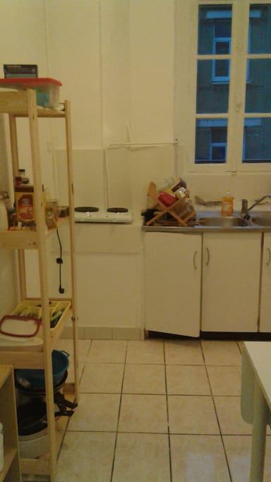 La cuisine: de la vaisselle, une table et des chaises, un four et une plaque de cuisson