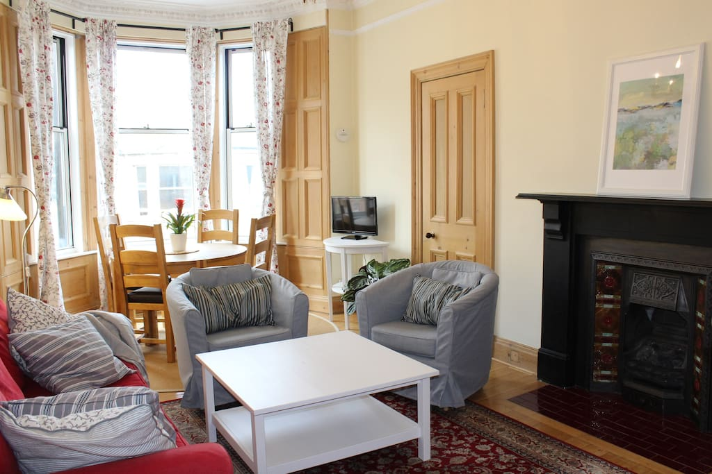 Bright and spacious, West-facing living room with living gas flame Victorian fireplace.