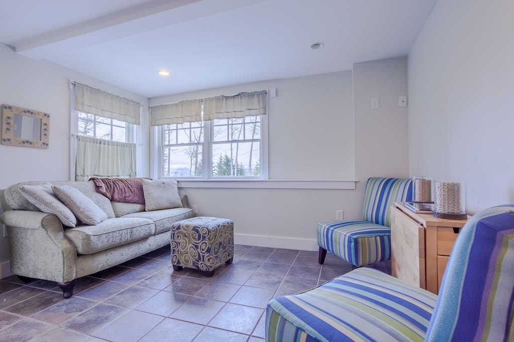 The sunlit living has a white comfy love seat and 2 decorative chairs.