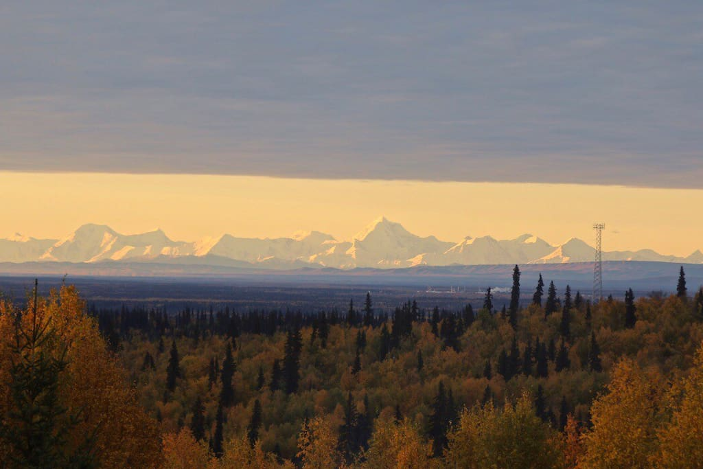 The zoomed view of the Alaska Range from our home in the fall.   Mount Hayes is the tallest middle peak.  The Tanana flats  misty purple blue in foreground.  In the evening the lights of North Pole can be seen.