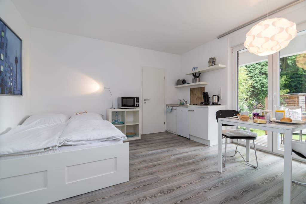 Doppelbett, Pantryküche und Essecke mit Blick in den Garten