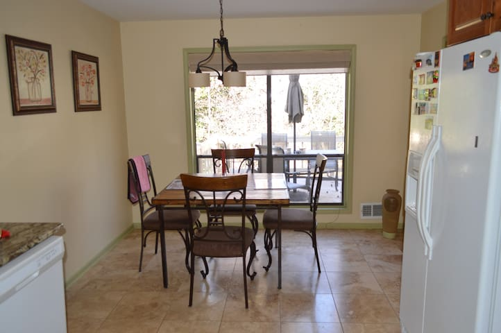 Kitchen leads from living room and also to outside deck with furniture and grill.