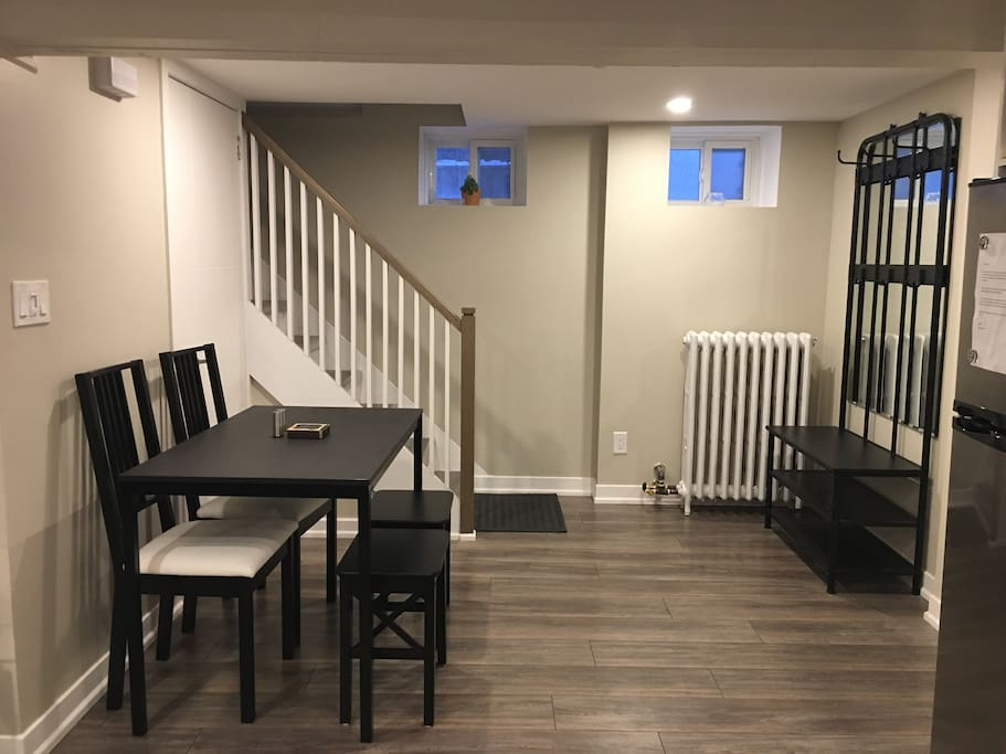 Coat and shoe rack at entrance followed by a dining table that seats four.