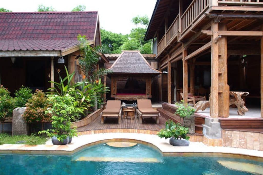 sunbathing areas and large pool, open air covered living area and kitchen.