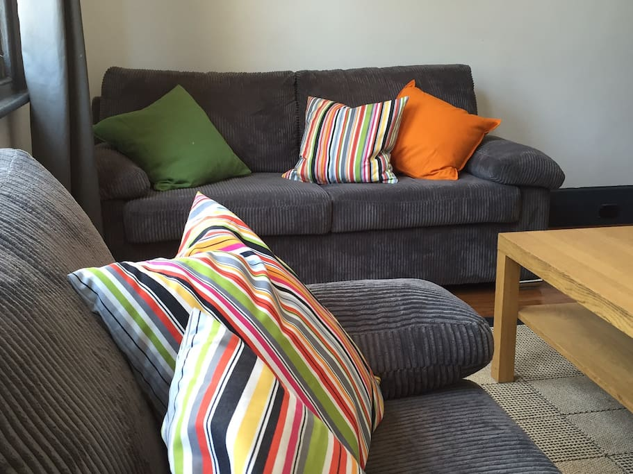 Soft couches and plenty of cushions! North facing windows gives the lounge room plenty of sunshine.