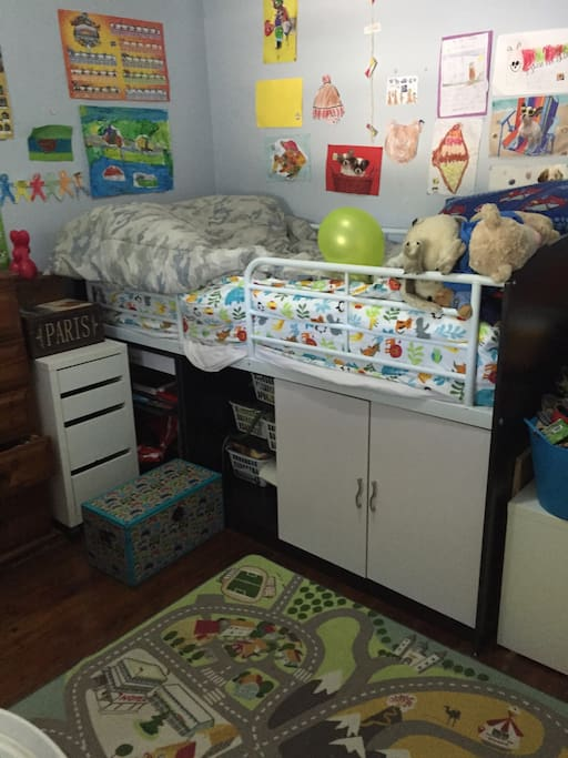 Large children's bedroom with bunk bed and extra mattress, toys and playing area