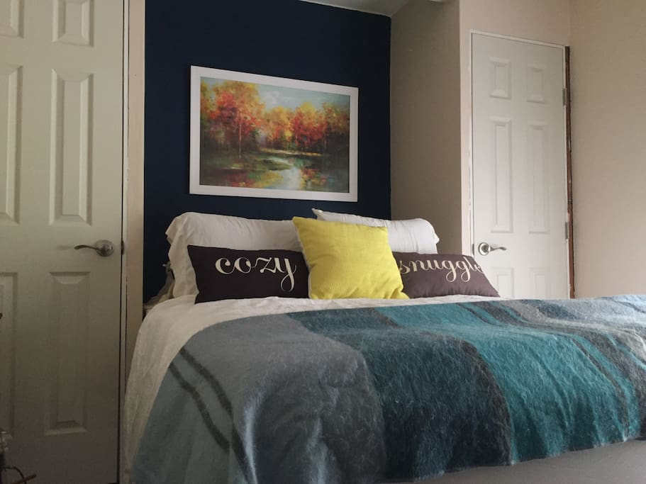 Second bedroom featuring neutral tones and a queen sized bed.