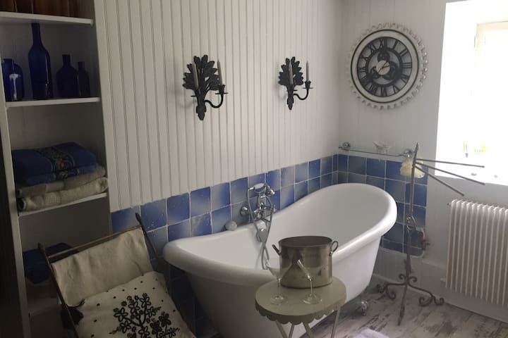 salle de bain très éclairée avec baignoire