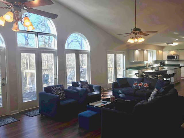 Spacious and luminous living room at the center of the property opening to the eat-in gourmet kitchen, the 4 bedrooms and a vast patio with a breath-taking waterfront view.