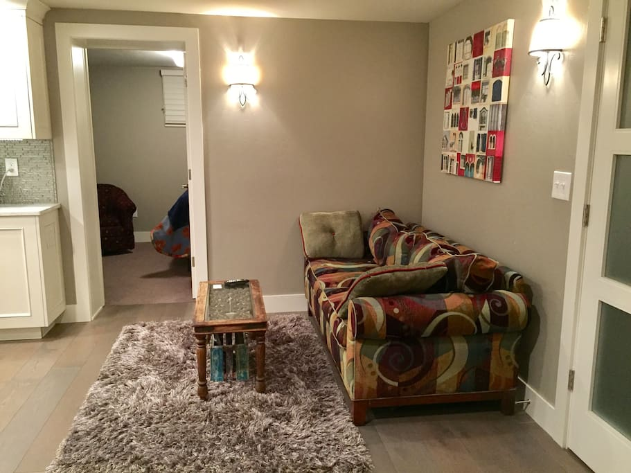 Living room w/small table, couch, kitchen, and basic cable TV