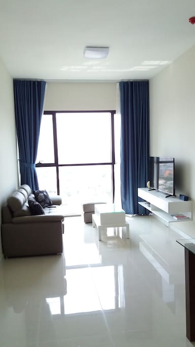 Spacious living room equipped with a comfy leather sofa, 48 inch smart TV & cable, coffee table and plant.