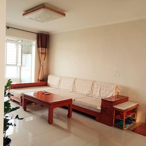 客厅宽敞明亮,采用全实木家具,坐在床上就能看见大海。
