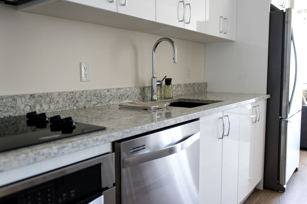 Quartz counter-tops with stainless steel appliances