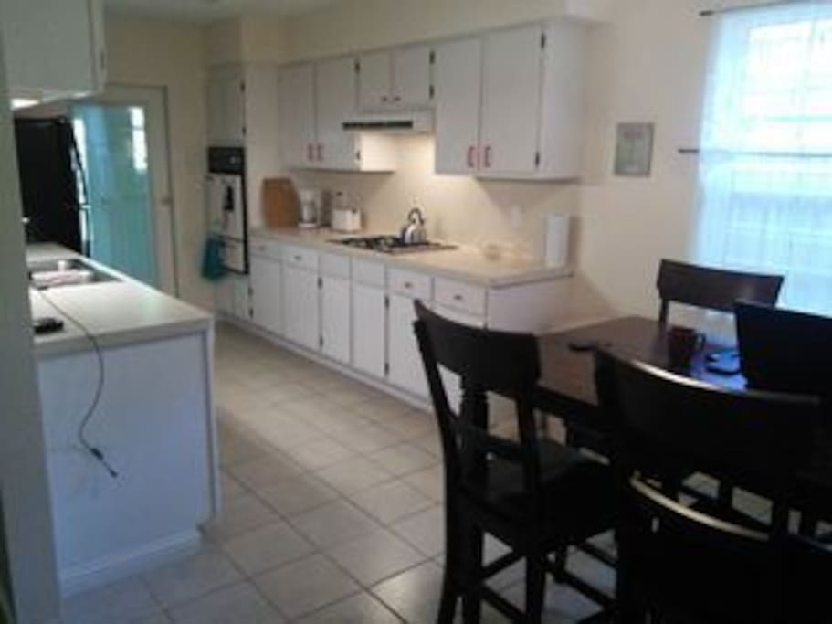 Kitchen with full size refrigerator, gas stove and double sink.