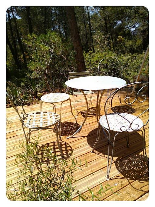 Terrasse en bois avec table chaises et balancelle. Plein sud.