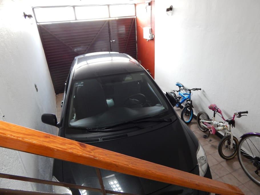 Garaje para 1 vehículo dentro de la casa con portón cerrado.