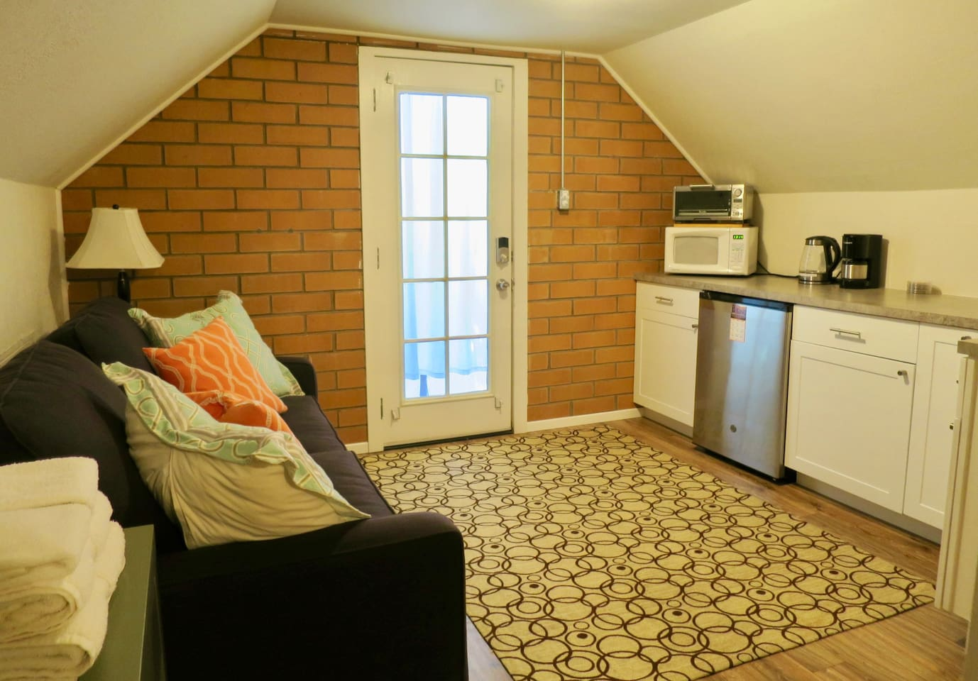 Living room area with kitchenette. Refrigerator, microwave, toaster oven, tea kettle, coffee maker & stainless kitchen sink. Also includes cutting board, plates, bowls, cups, mugs and utensils.  Please note: There is NO TV in the suite