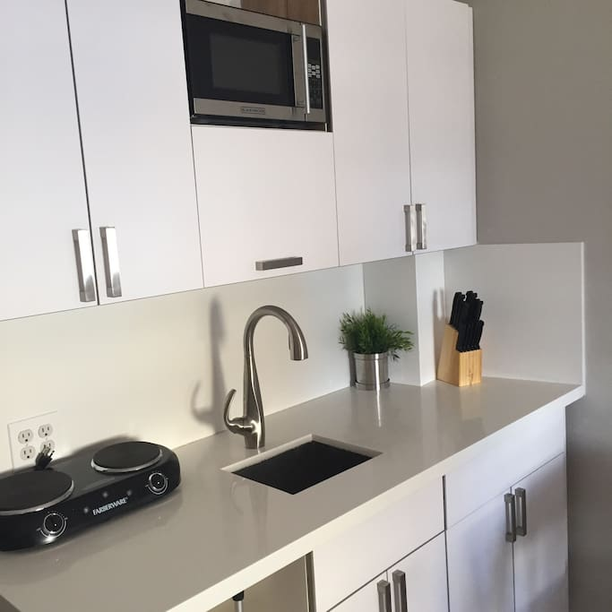Cooking area with new Quartz countertops : microwave, refrigerator, coffe maker, electric stove and many others