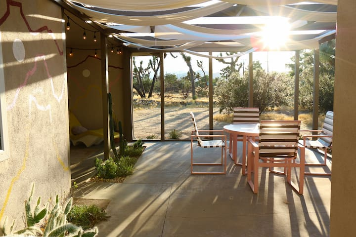 Watch the sun set behind the mountains from our amazing backyard patio. The property is peppered with Joshua trees, cholla cactus, and blooming desert plants.