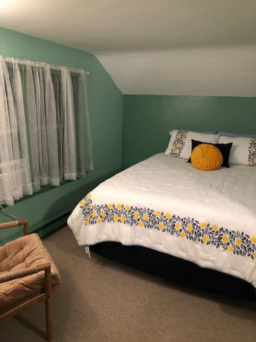 The Queen room has a queen size bed and air conditioner.