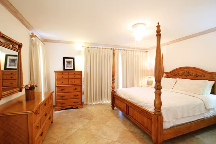 The master bedroom with a king bed, a/c, ceiling fan and en suite bathroom