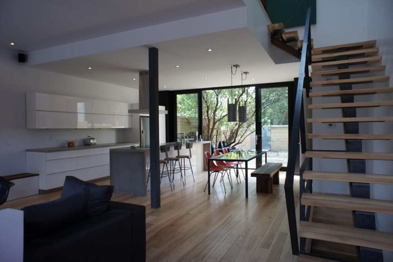 Espace de vie au RDC ouvert et lumineux, design épuré. Open living space on first floor