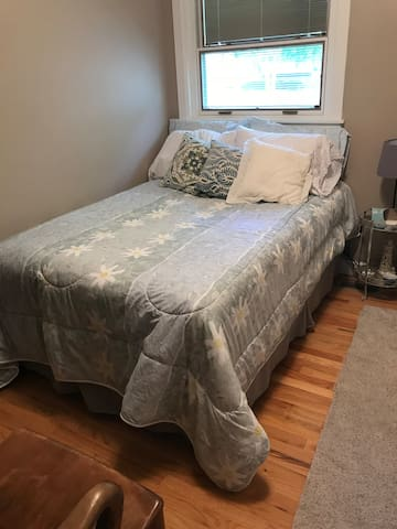 The bedroom has a double bed, empty dresser and closet ready for your belongings. There are a mirror and towel hooks on the back of the door.