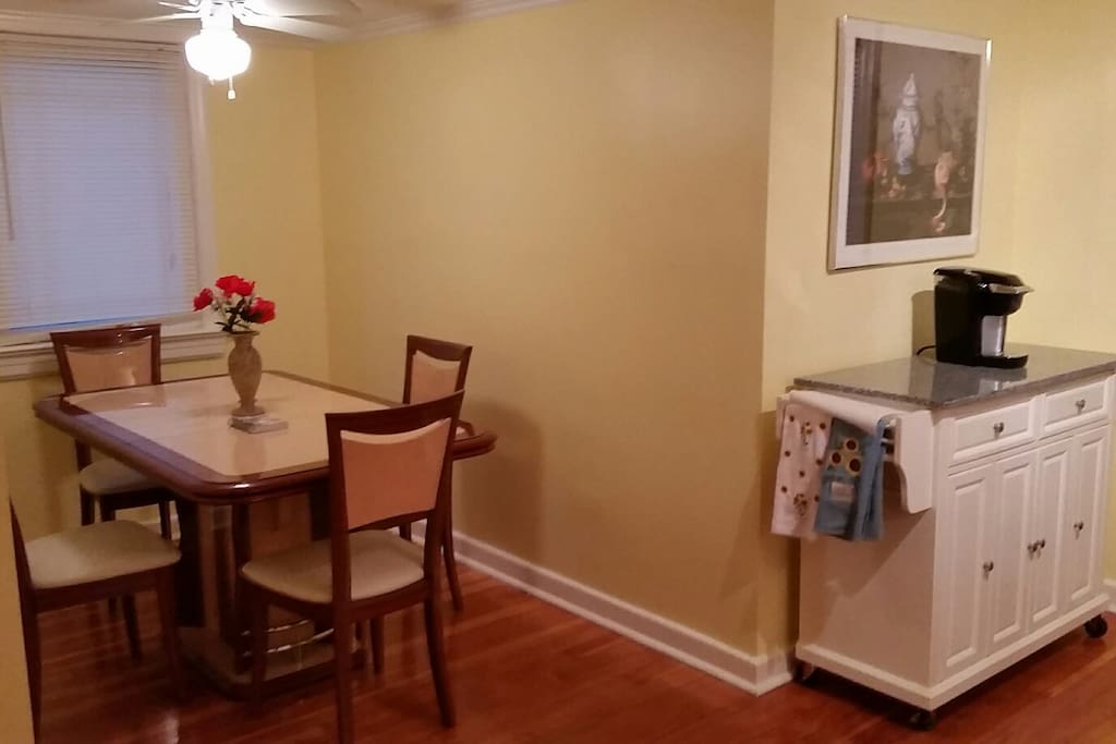 Dining Room/kitchen, expandable table, movable marbletop cabinet, Keurig coffee maker.  Hot plates are stored in an adjacent closet, with cooking utensils, etc.