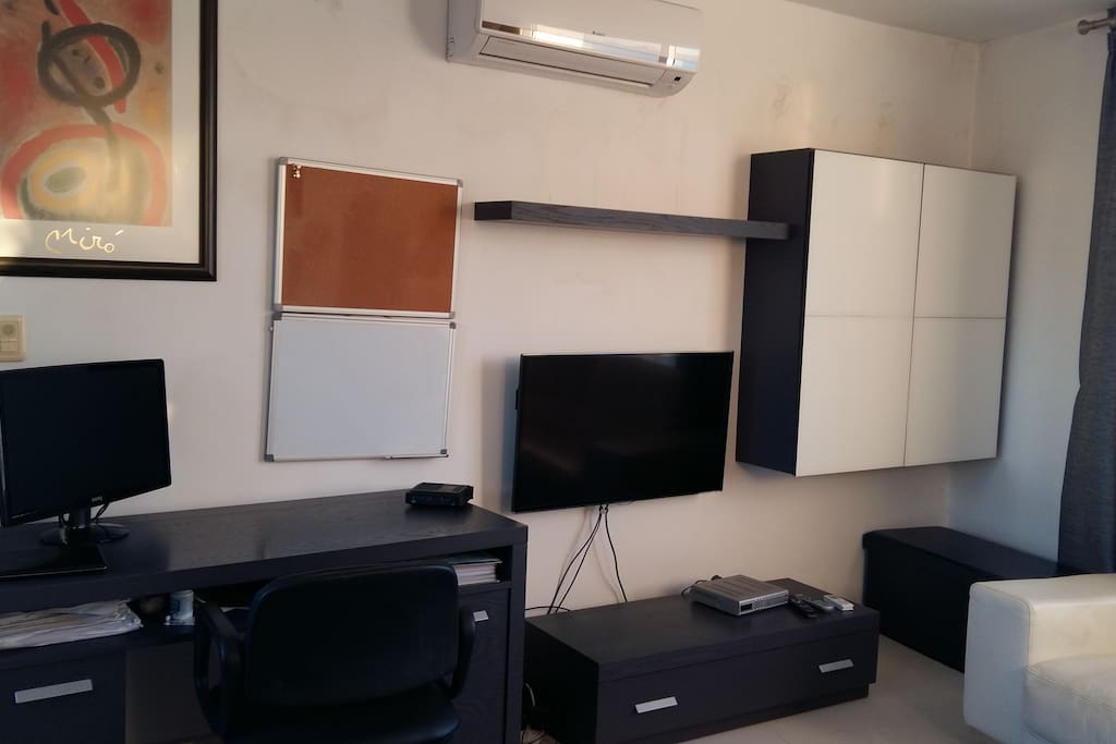 Living area with desk, TV, sofa, air-condition and storage