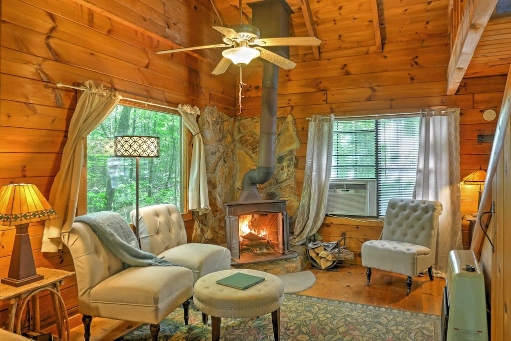 Rustic wood paneling throughout, a wood-burning fireplace, and cozy, plush furnishings create a warm environment.
