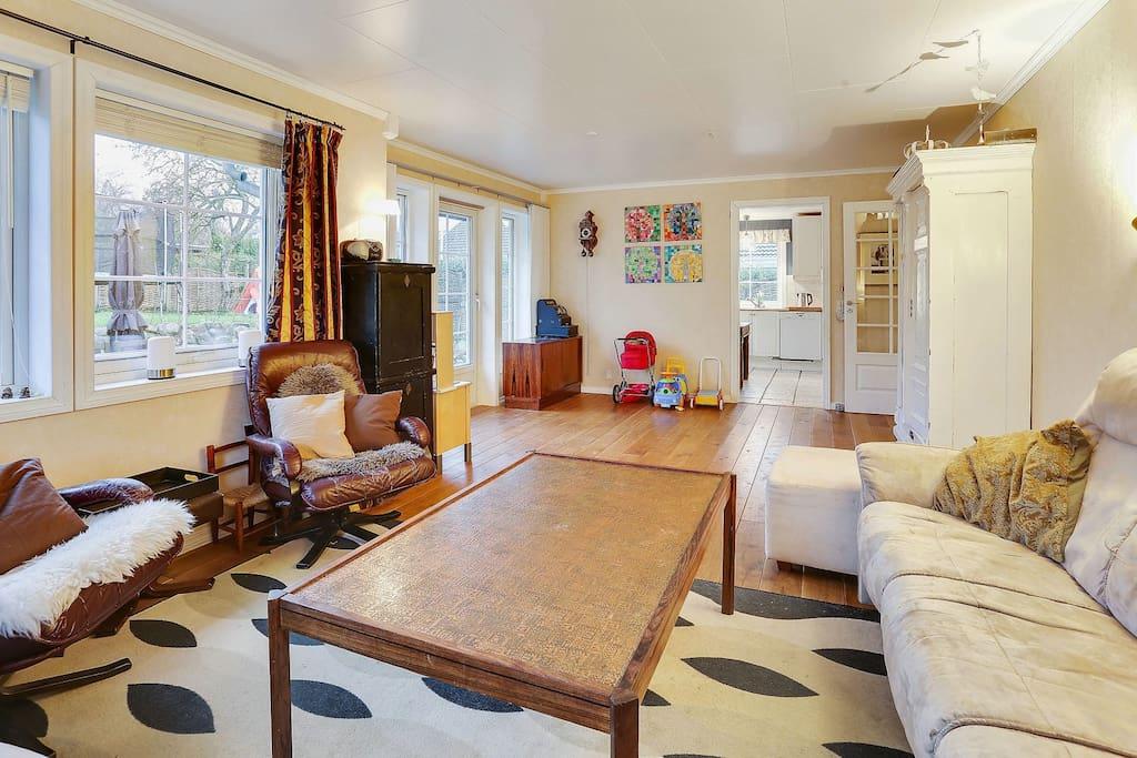 Stor og funktionelt stue med adgang til haven, entré og køkken
