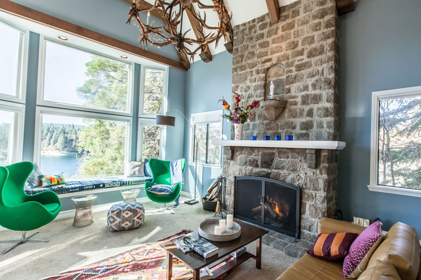 Living room with fireplace surrounded by natural stone