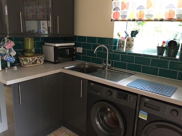 Kitchen area with fridge, washing machine, tumble drier, mini oven and induction hob.