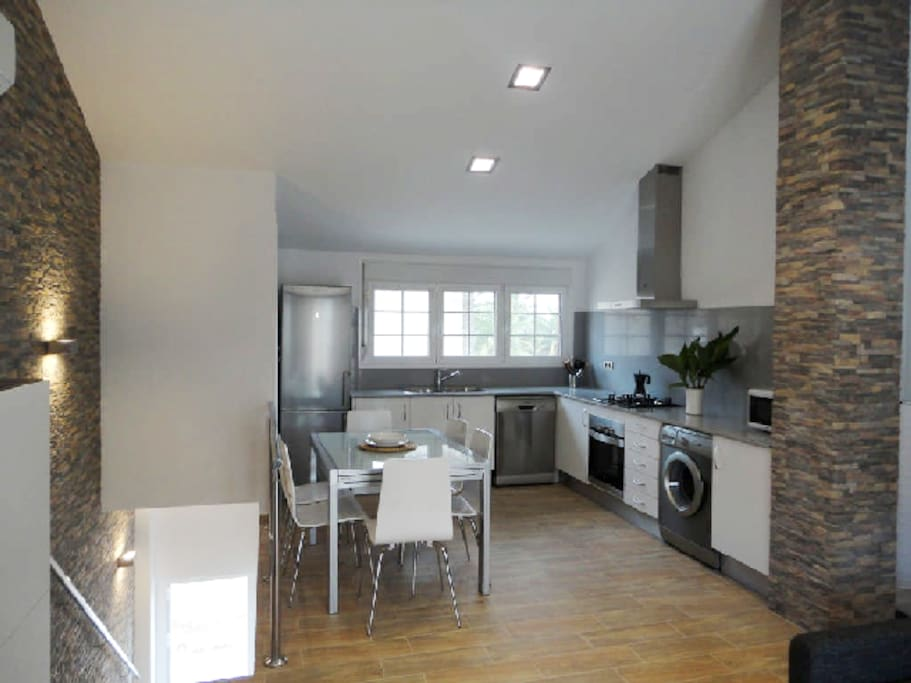 Moderna cocina equipada y comedor con mucha luz
