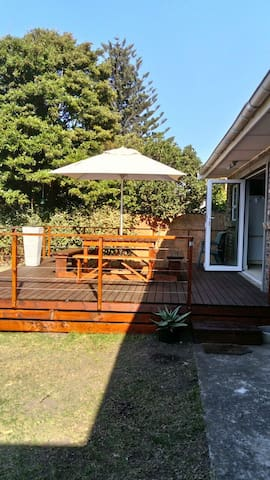 Side view of deck that leads from kitchen through sliding stacker doors. 12 Seater wooden table/bench set with outdoor unbrella