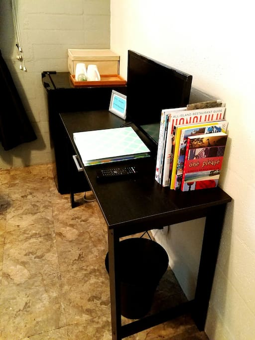 Computer desk with smart TV, reading material, WiFi password, and welcome binder