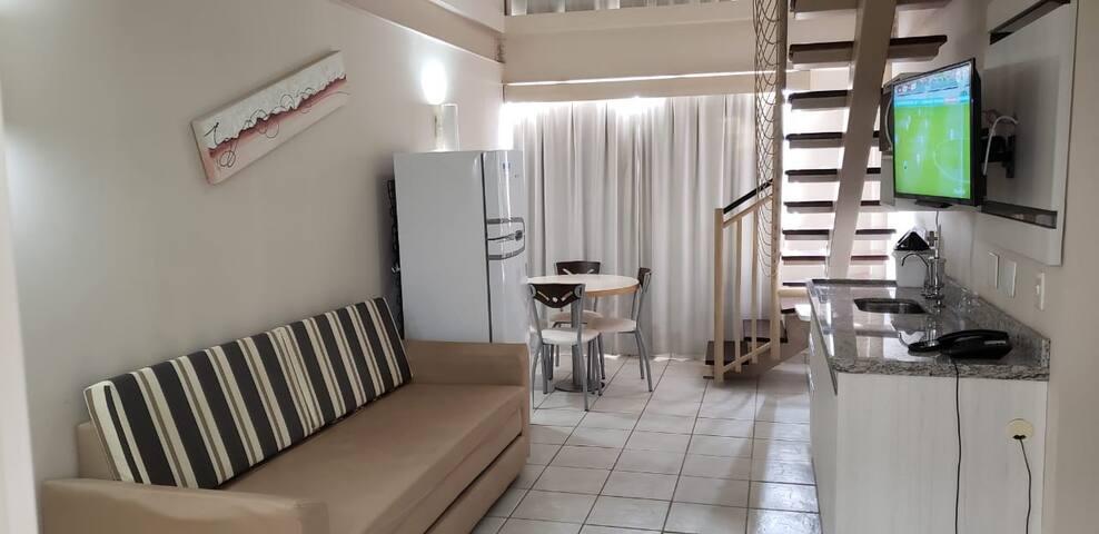 Sala de estar com TV de tela plana, sofá de dois lugares, sofá-cama para 2 pessoas, geladeira, microondas  e mesa com 4 cadeiras