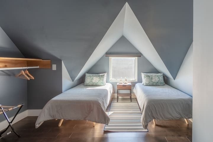 This charming bedroom features two twin beds, a closet to hang your cloth, and a luggage rage to place your suitcase on, and for those mornings that you would like to sleep in, the large window has blackout blinds.