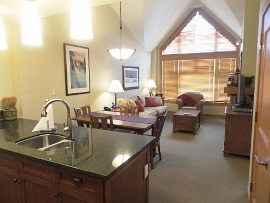 Large open vaulted high ceiling Living Room with Queen Size Sleeper sofa, fireplace, and Flat Screen HD TV.