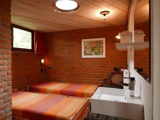 Slaapkamer met twee éénpersoons bedden en wastafel