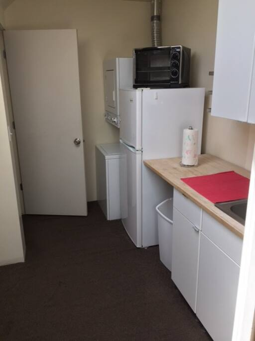Kitchen with refrigerator/freezer, microwave oven, sink, and washer/dryer