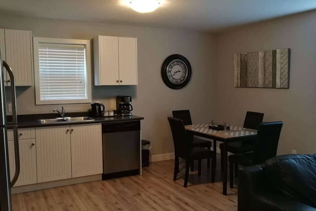 Modern dining and kitchen with 4 stainless steel appliances.