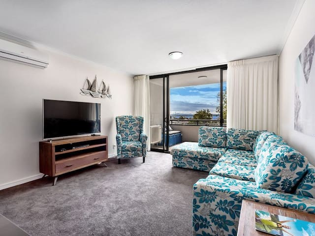 Spacious lounge room with direct access to the balcony. The lounge room offers a 65 inch Smart TV with Netflix and selected Foxtel channels. Free Wi-Fi and air conditioning