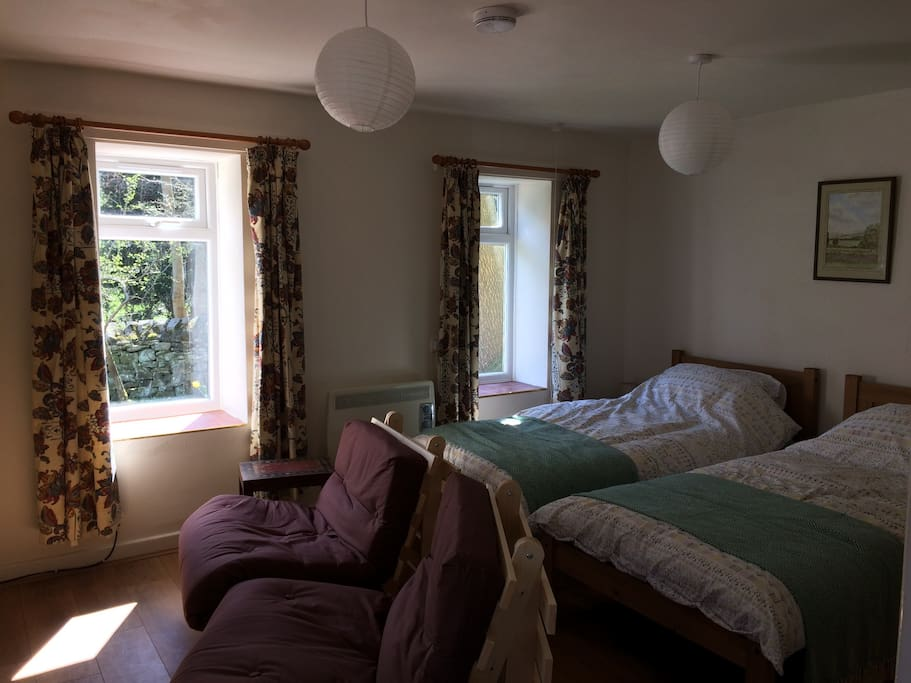Living room - studio accommodation, twin beds, chairs & t.v & wall heater